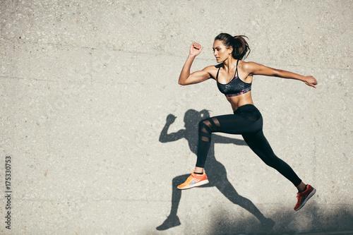 Dysponowana młoda kobieta skacze i biega