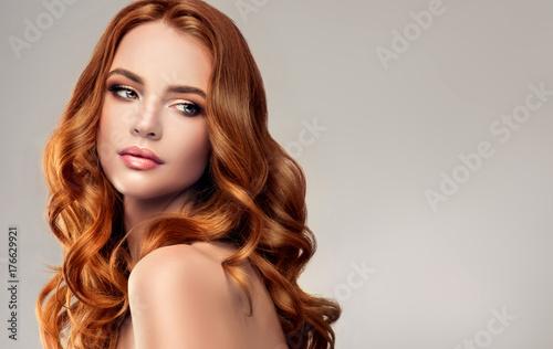 Piękna modelka z długimi rudymi kręconymi włosami. Czerwona głowa. Produkty do pielęgnacji i urody