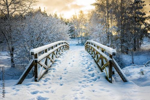 Śnieżny, drewniany most w zimowy dzień. Stare Juchy, Polska