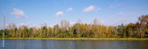 Piękny wiejski krajobraz zawierający las, niebo oraz wodę - jesienny pejzaż ze Stawów Milickich