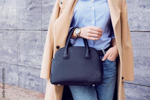 Modna kobieta w beżowym płaszczu i dżinsach z czarną dużą torbą