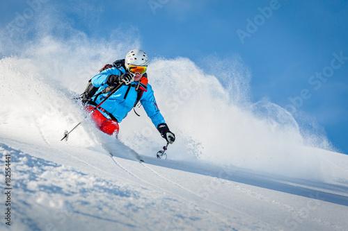 Mężczyzna narciarz freeride w górach poza trasą