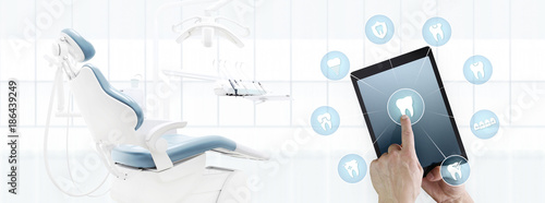 dentist hand touch digital tablet screen teeth icons and symbols on dental clinic with dentist's chair background web banner template contact us concept