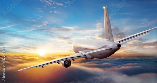 Komercyjny samolot odrzutowy lata nad chmury w pięknym zmierzchu świetle.