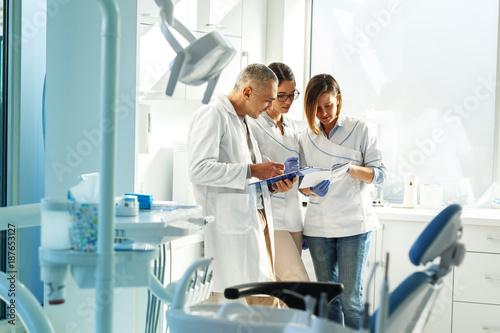 Zespół dentystów medycznych w gabinecie stomatologicznym dyskutuje o praktyce i badaniu listy pacjentów.