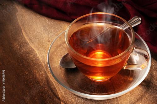 czarna herbata świeżo parzona w szklanej filiżance, parujący gorący napój na ciemnym rustykalnym drewnie, miejsce