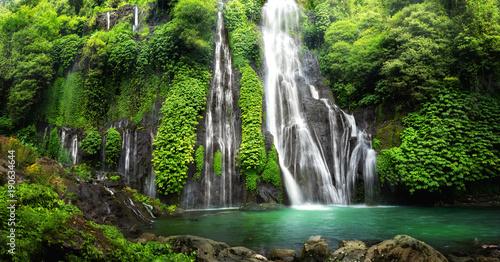 Kaskada wodospadu w dżungli w tropikalnym lesie deszczowym ze skałą i turkusowym błękitnym stawem. Nazwa Banyumala, ponieważ jest to bliźniaczy wodospad na zboczu góry