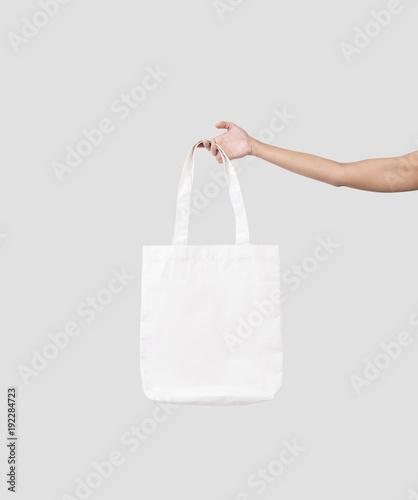 ręka trzyma worek płótno tkaniny do makiety pusty szablon na białym tle na szarym tle.