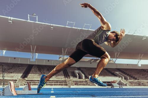 Sprinter startujący z bloku startowego na bieżni