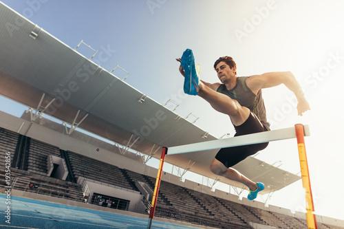 Sportowiec przeskakując przeszkodę na bieżni