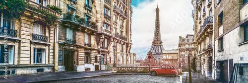 Wieża Eiffla w Paryżu z małej ulicy z zabytkowym czerwonym samochodem 2cv
