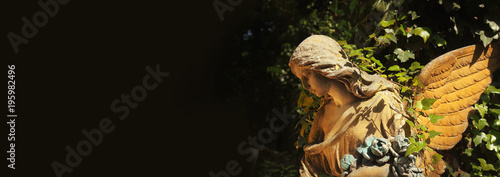 Antique statue of gold angel in the sunlight with place for text and designer. (religion, faith, death, resurrection, eternity concept)