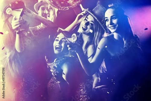 Grupa taneczna ludzie tańczą. Kobiety i mężczyźni bawią się w klubie nocnym. Odpocznij po ciężkim dniu w pracy. Podświetlenie włosów dziewcząt. Ludzie tańczą pod wpływem alkoholu. Tonowanie i rozmycie tła.
