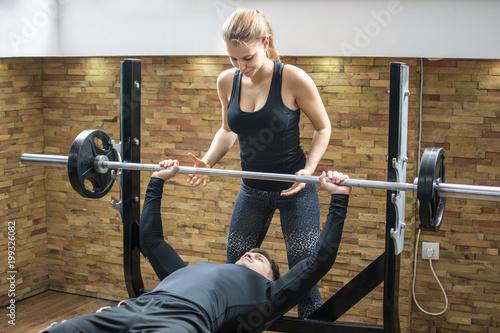 Młody człowiek podnoszenia ciężarów z pomocą atrakcyjnej dziewczyny w siłowni.