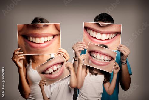 młoda rodzina z dziećmi trzyma zdjęcie uśmiechnięte usta na szarym tle