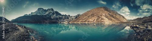 Spektakularne krajobrazy krystalicznie czystego jeziora Gokyo na potężnym, ośnieżonym tle Himalajów. Siła i piękno dzikiej dziewiczej przyrody. Idealny obraz do tła i tapet.