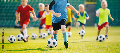 Trening piłkarski dla dzieci. Trening piłkarski dla dzieci. Dzieci biegają i kopią piłki. Młodzi chłopcy doskonalą umiejętności piłkarskie