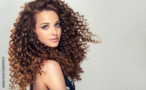 Brunetka dziewczynka z długie i lśniące kręcone włosy. Piękna wzorcowa kobieta z falistą fryzurą