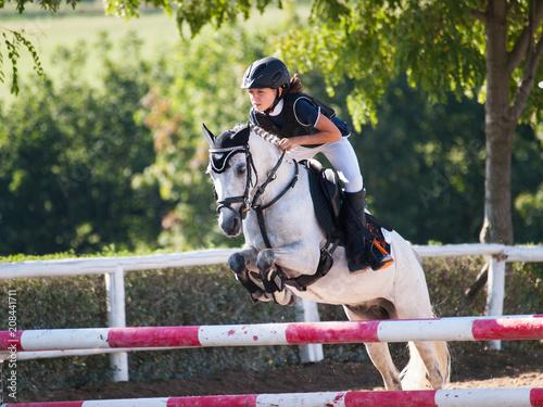 Dziewczyna z białym kucyka skoki przez przeszkodę w konkurencji koni