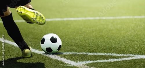 Stopa piłkarza dziecięcego i piłki na boisku piłkarskim, kopiąc z rzutu rożnego