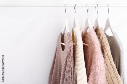 Ciepłe dzianinowe, jesienne, zimowe ubrania wiszące na stojaku, modny trend, pastelowe kolory