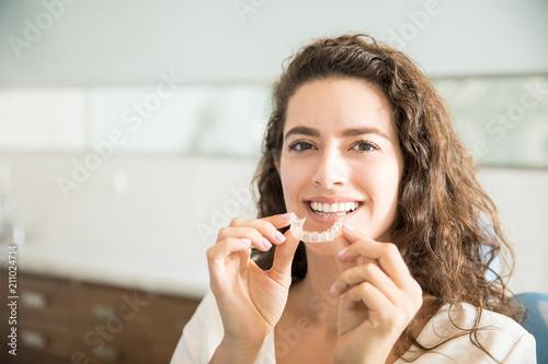 Piękny pacjent trzyma ortodontyczne elementy ustalające w klinice dentystycznej