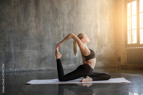 Młoda kobieta robi ashtanga praktyki jogi w studio na poddaszu, w otoczeniu jasnego światła słonecznego. Piękna dziewczyna medytuje, czyni się zdrowym ciałem i wzmacnia ducha.