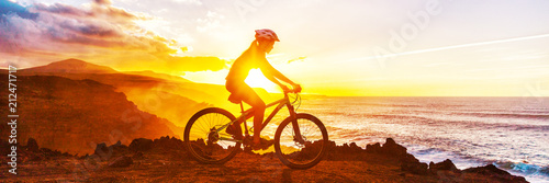 Mountain biking cyclist riding bike on coast trail against sunset. Silhouetter of woman doing sports outdoors banner panorama. Active lifestyle.