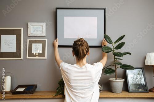 Dziewczyna wiesza ramę na szarej ścianie
