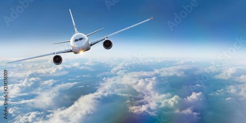Samolot komercyjny lecący ponad dramatyczne chmury.