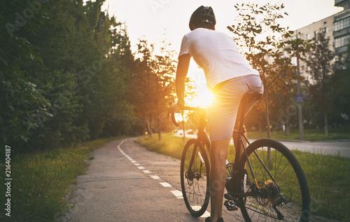 Młody chłopak w zwykłym ubraniu jeździ na rowerze po mieście wieczorem