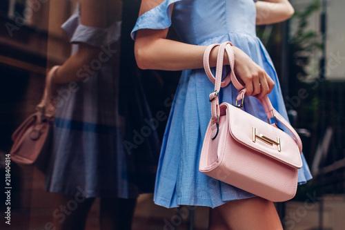 Close-up of stylish female handbag. Fashionable woman holding beautiful accessories outdoors.
