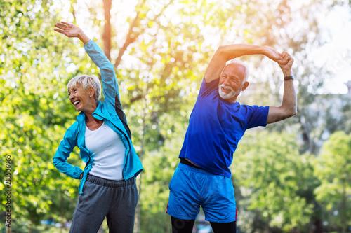 Szczęśliwa dysponowana starsza para ćwiczy w parku.