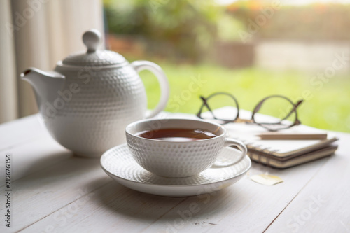 Cup of tea on white wooden table with nature background