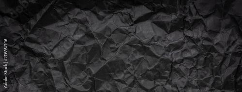 Ragged crumpled dark black paper texture background