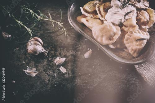 Rustykalne pierogi ruskie z rozmarynem leżące na starym talerzu