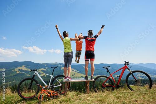 Widok z tyłu rowerzystów rodzinnych, mama, tata stojący na drewnianej ławce z podniesionymi rękami, trzymając dziecko w powietrzu, odpoczywając po rowerach w górach. Aktywny styl życia i koncepcja szczęśliwych relacji.