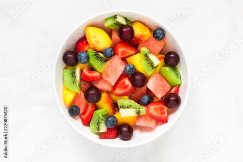 Puchar zdrowa świeża owocowa sałatka na bielu marmuru tle. zdrowe jedzenie