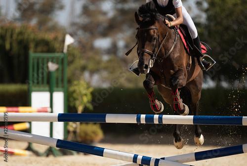 Dżokej na koniu skacze przez przeszkodę, przeskakując przeszkodę podczas zawodów