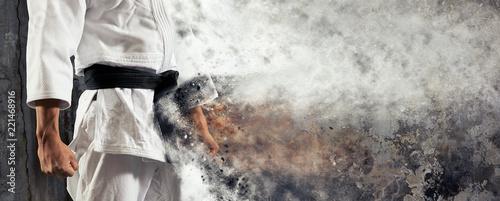 Facet pozuje w białym kimonie z czarnym pasem. Sztandar w Judo