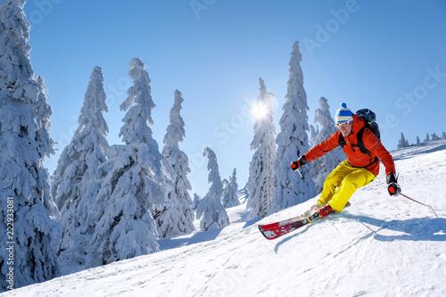 Narciarz zjazd na nartach w wysokich górach przeciw błękitne niebo
