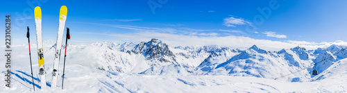 Narty w sezonie zimowym, góry i sprzęt narciarski na szczycie w słoneczny dzień we Francji, w Alpach ponad chmurami.