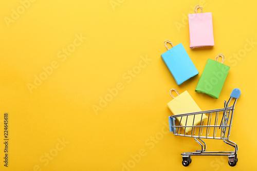 Mali papierowi torba na zakupy z wózek na zakupy na żółtym tle
