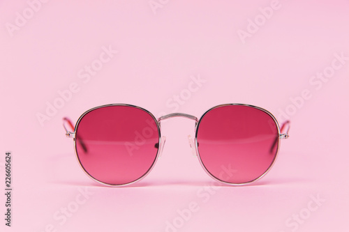 Pink sunglasses on pink background. Isolated on pink. Fashion and style