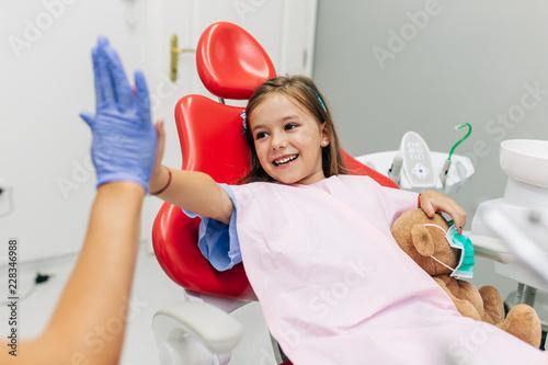 Śliczny małej dziewczynki obsiadanie na stomatologicznym krześle i mieć stomatologicznego traktowanie.