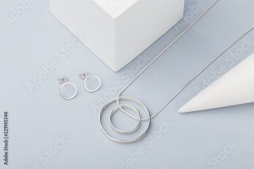 Minimalist geometric silver necklace and circle stud earrings on gray background