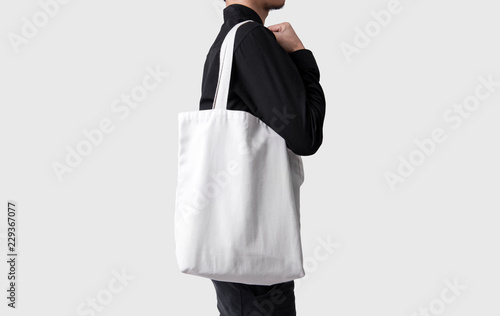 Mężczyzna trzyma worek płótno tkaniny dla makieta pusty szablon na białym tle na szarym tle.