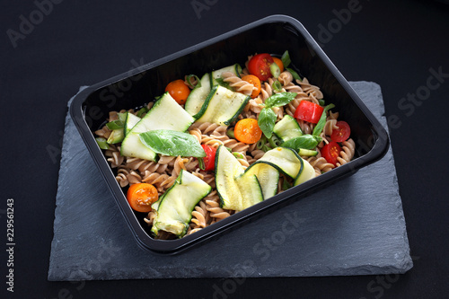 Dieta pudełkowa. Sałatka makaronu z cukinią i pomidorami podana w naczyniu jednorazowym.