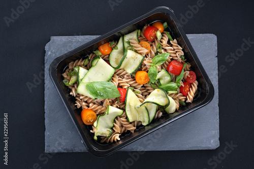 Catering dietetyczny. Sałatka makaronu z cukinią i pomidorami podana w naczyniu jednorazowym.