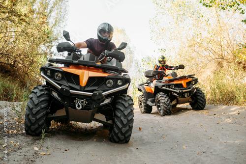 Dwóch motocyklistów jeździ w lesie, widok z przodu
